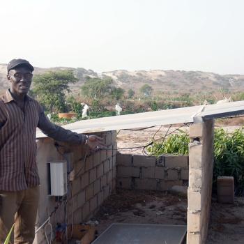 Mamadou Kante devant l'installation solaire